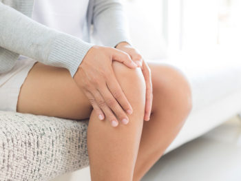 Patient holding her knee in pain before a stem cell lift to the joints